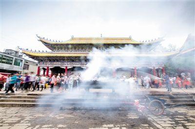 工作人员用水浇灭香炉内燃烧的香纸