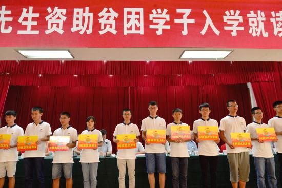 来自江西省25个贫困县的贫困学生代表上台领取助学金。