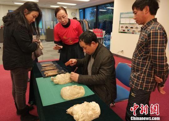 """""""中国民间工艺美术师""""罗春明在现场还进行了傩面具雕刻及展示,引得市民驻足观看。 平懿 摄"""