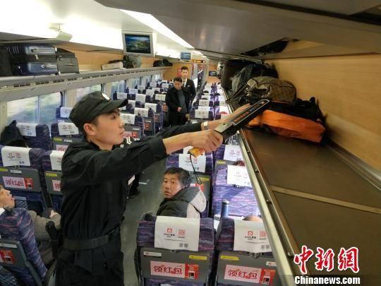"""南昌客运段动车一队""""00后""""列车安全员李可平正在检验旅客行李。 姜涛 摄"""