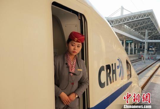 """南昌客运段动车一队""""00后""""乘务员辛鑫站在车厢门口察看旅客上车情况。 姜涛 摄"""