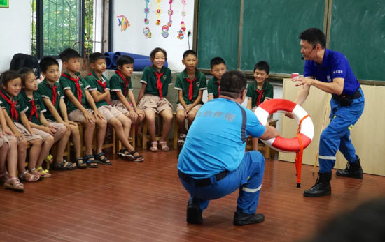 6月22日,青山湖区水上救援工作人员给孩子们介绍游泳圈的相关知识。