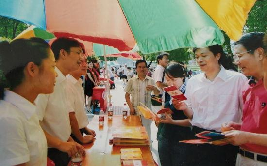 """2009年8月,农行赣州分行青年志愿者在中心城区开展""""送金融知识进社区""""金融宣传活动。(欧敏婕供图) 十"""