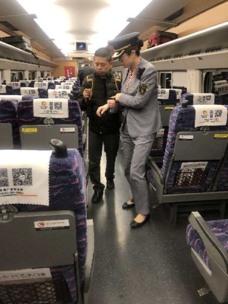 南昌客运段动车二队西动9组的乘务员在值乘中为盲人旅客提供一对一服务时的情景