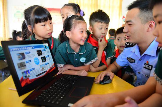 江西省赣州市会昌县希望小学的学生向网安大队民警咨询生活中遇到的网络安全问题。