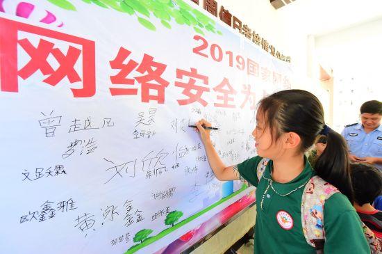 """会昌县希望小学的学生在""""网络安全宣传周""""画布上签名承诺""""从小争做好网民"""""""