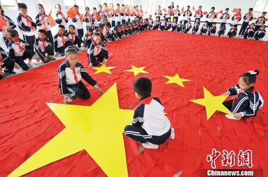 龙8国际娱乐手机登录小学生千条红领巾拼巨型国旗迎国庆